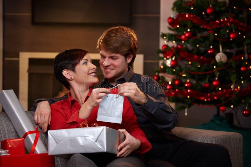 Het gelukkige paar dat Kerstmis geeft stelt voor stock afbeeldingen