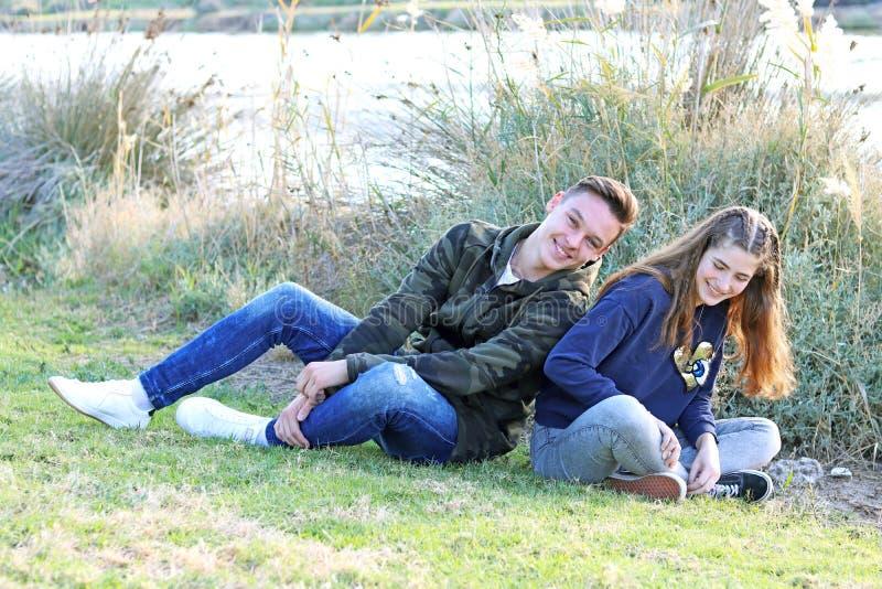 Het gelukkige paar die van de tienerleeftijd pret in het park hebben stock fotografie