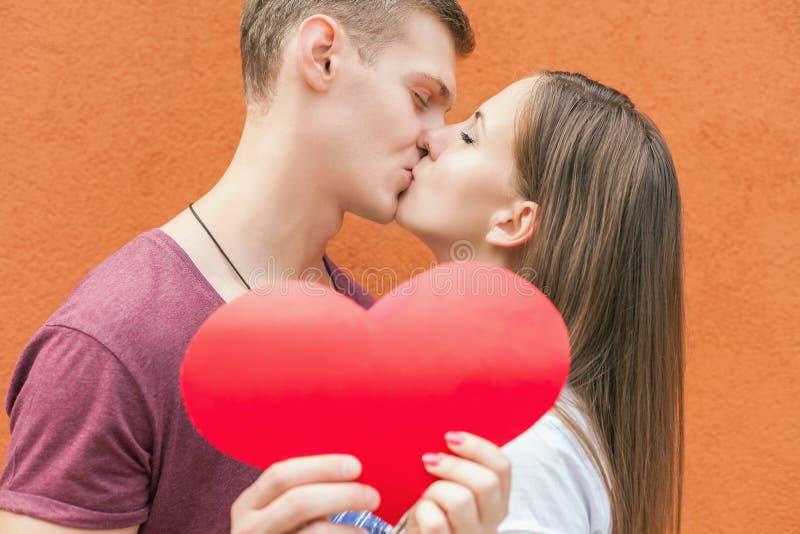 Het gelukkige paar die van de Valentijnskaartendag rood hartsymbool houden royalty-vrije stock fotografie