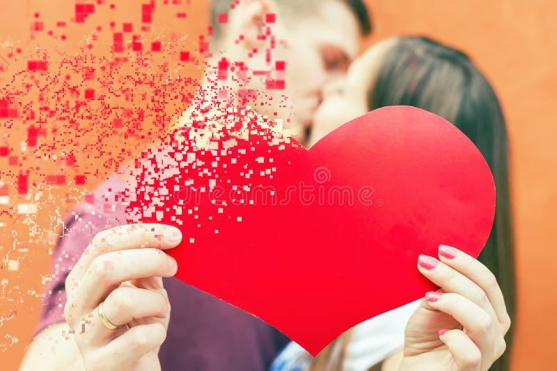 Het gelukkige paar die van de Valentijnskaartendag rood hartsymbool houden stock afbeelding