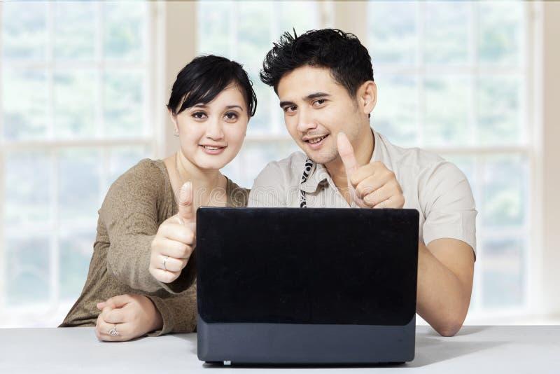 Het gelukkige paar en laptop tonen beduimelt omhoog stock afbeeldingen