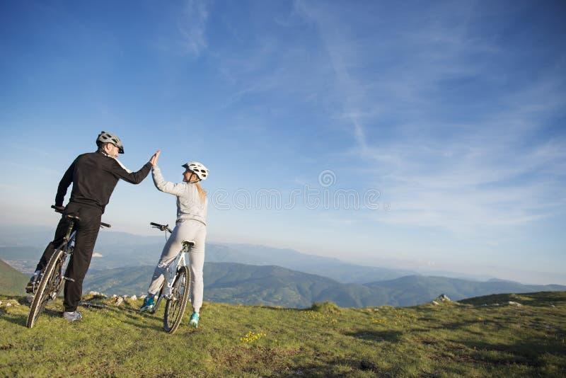 Het gelukkige paar gaat op een weg van het bergasfalt in het hout op fietsen met helmen die elkaar een hoogte vijf geven stock fotografie