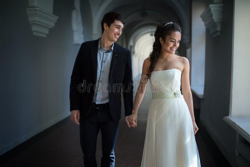 Het gelukkige paar gaat speels onderaan een lange gang royalty-vrije stock fotografie