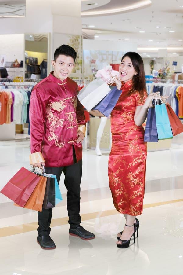 Het gelukkige paar houdt het winkelen zakken in een wandelgalerij royalty-vrije stock foto
