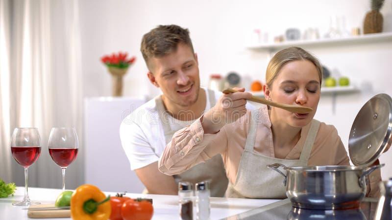 Het gelukkige paar koken samen in keuken, vrouwelijke proevende soep, gezond voedsel stock foto