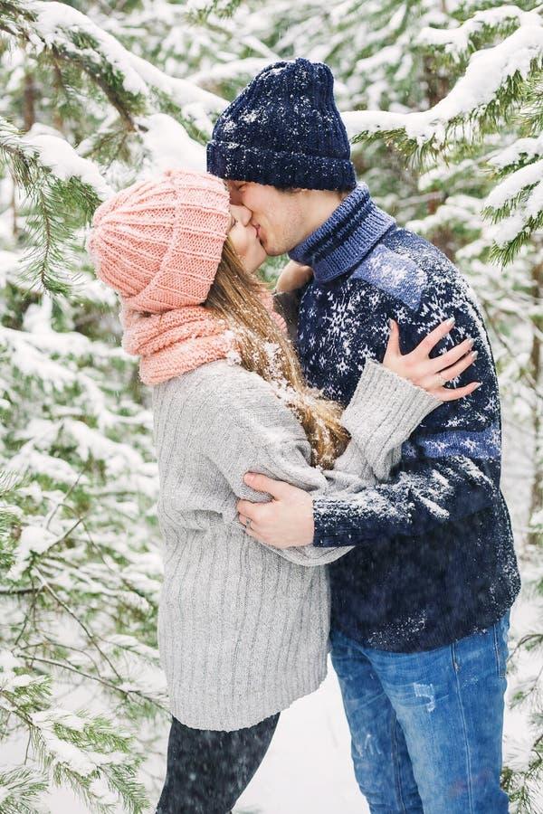 Het gelukkige paar kussen in de winterbos en sneeuwval stock afbeelding