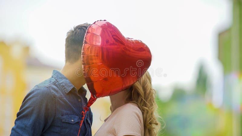 Het gelukkige paar kussen, die achter hartballon verbergen, romantische verhouding, datum royalty-vrije stock afbeeldingen