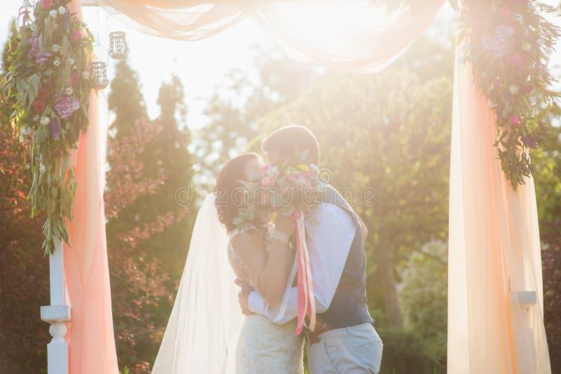 Het gelukkige paar kussen onder de textielboog royalty-vrije stock afbeelding