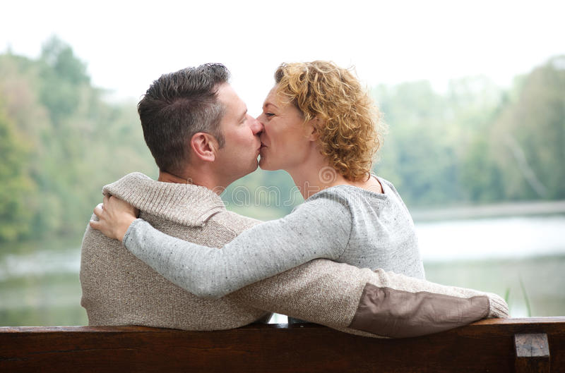 Het gelukkige paar kussen op parkbank stock fotografie