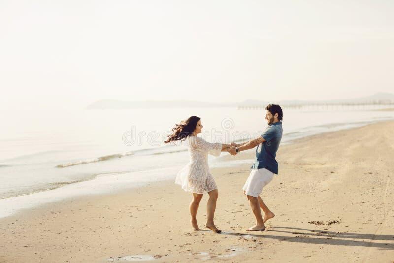 Het gelukkige paar in liefde heeft pret op het strand Zij springen, lachen en genieten van het overzees royalty-vrije stock afbeeldingen