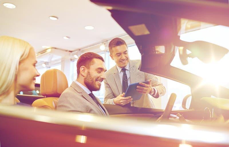 Het gelukkige paar met autohandelaar in auto toont of salon royalty-vrije stock afbeeldingen
