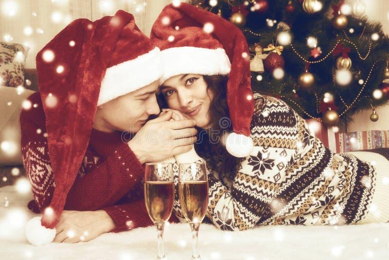 Het gelukkige paar met champagne ligt thuis dichtbij Kerstmisboom en decoratie De wintervakantie en liefdeconcept gestemd geel stock afbeeldingen