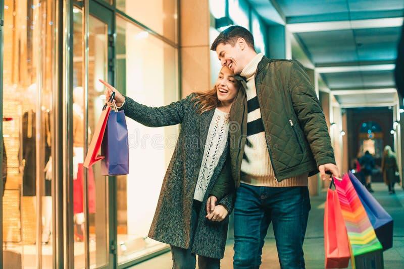 Het gelukkige paar met het winkelen doet het genieten van van nacht bij stadsachtergrond in zakken stock fotografie