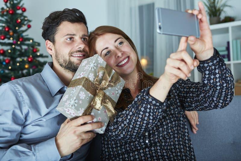 Het gelukkige paar neemt een selfie met gift royalty-vrije stock foto's