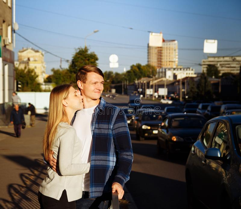 Het gelukkige paar omhelst in de straat, dichtbij de rijweg tribune dichtbij de omheining naast de rijweg royalty-vrije stock afbeelding