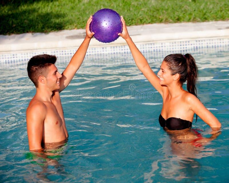 Het gelukkige paar ontspannen in de pool die met een bal spelen royalty-vrije stock fotografie