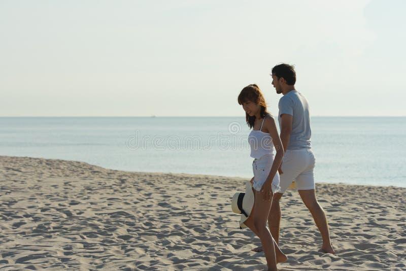 Het gelukkige paar ontspannen op strand bij zonsopgang, achtermening stock afbeelding