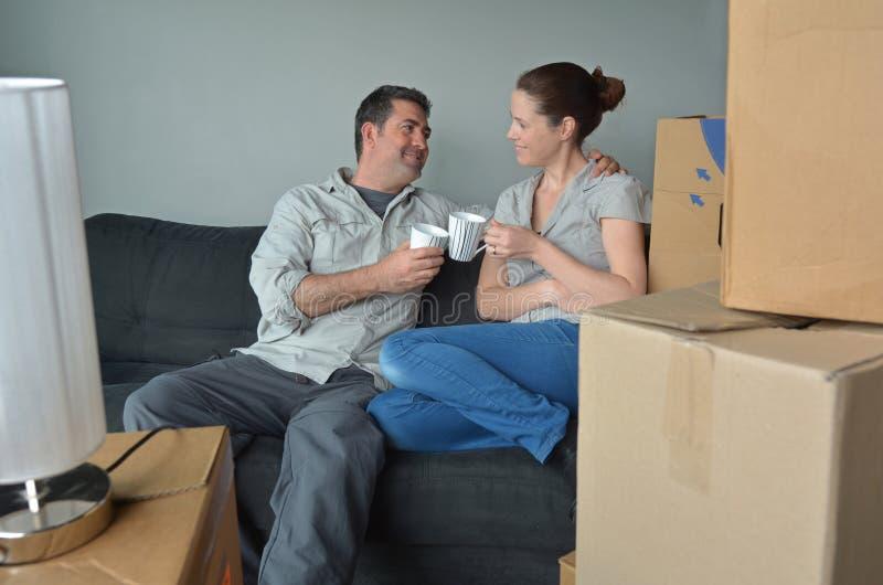 Het gelukkige paar ontspant op een bank tijdens een beweging in een nieuw huis royalty-vrije stock afbeelding