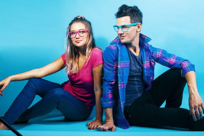 Het gelukkige paar samen stellen vrolijk op blauwe achtergrond die glazen, kerel en studentes samen vrienden dragen royalty-vrije stock foto's