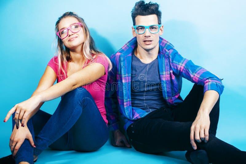 Het gelukkige paar samen stellen vrolijk op blauwe achtergrond die glazen, kerel en studentes samen vrienden dragen royalty-vrije stock foto