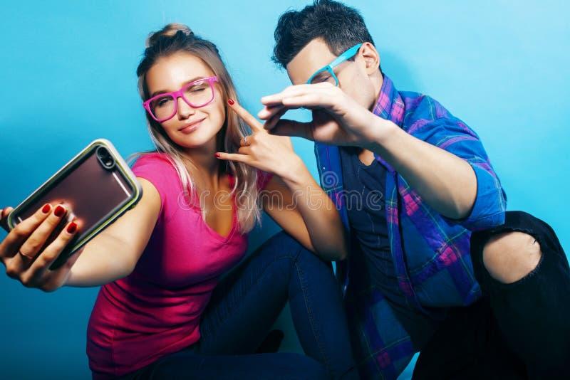 Het gelukkige paar samen stellen vrolijk op blauwe achtergrond die glazen, kerel en studentes samen vrienden dragen stock afbeelding
