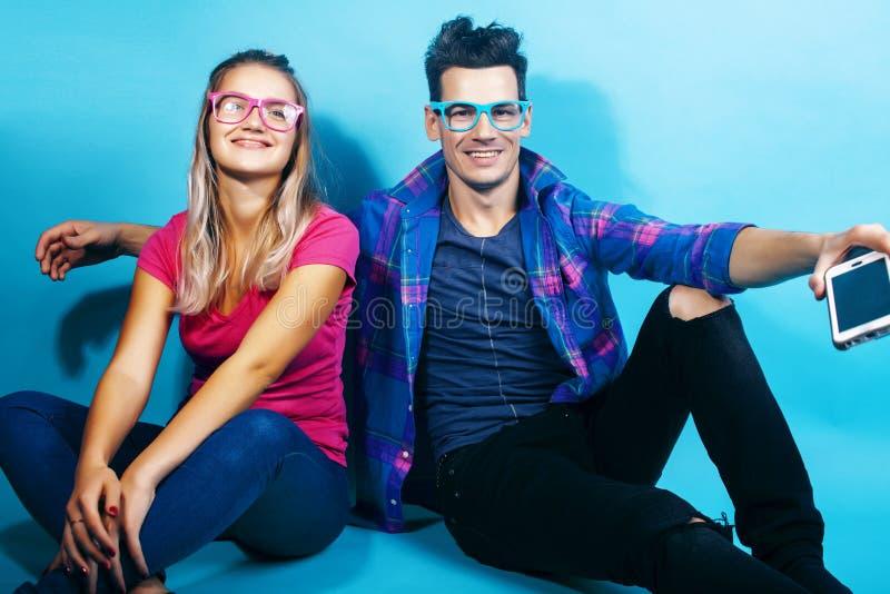 Het gelukkige paar samen stellen vrolijk op blauwe achtergrond die glazen, kerel en studentes samen vrienden dragen royalty-vrije stock afbeelding