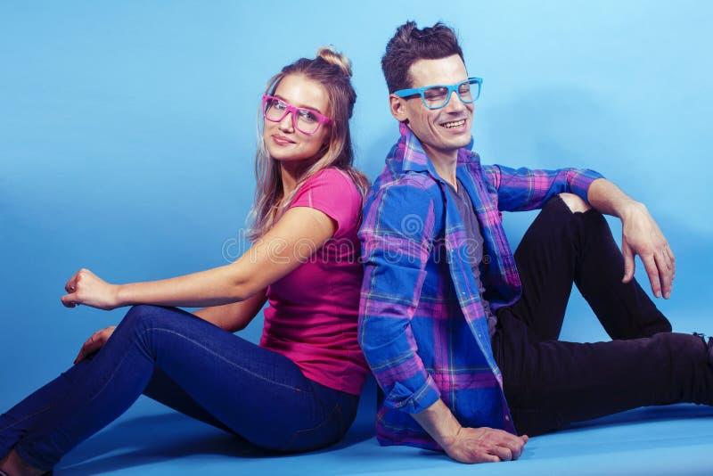 Het gelukkige paar samen stellen vrolijk op blauwe achtergrond die glazen, kerel en studentes samen vrienden dragen stock afbeeldingen