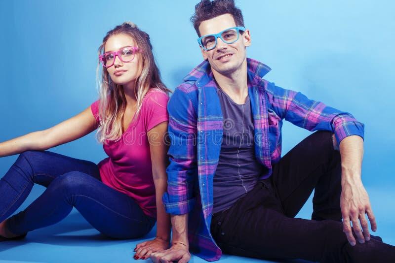Het gelukkige paar samen stellen vrolijk op blauwe achtergrond die glazen, kerel en studentes samen vrienden dragen stock fotografie