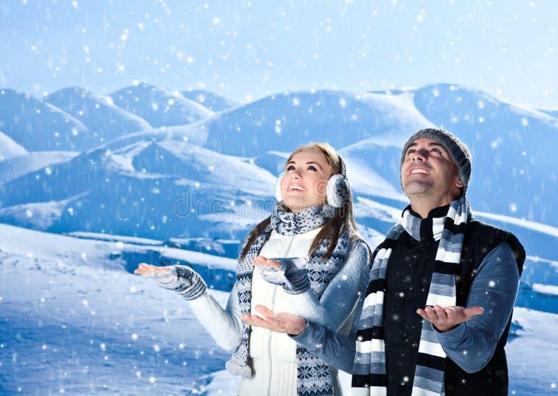 Het gelukkige paar spelen openlucht bij de winterbergen stock fotografie
