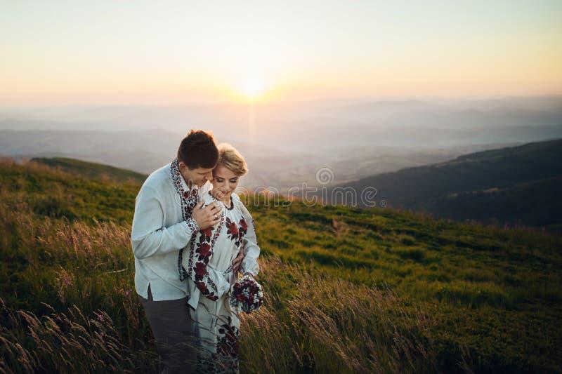 Het gelukkige paar stellen bij bergen stock afbeelding