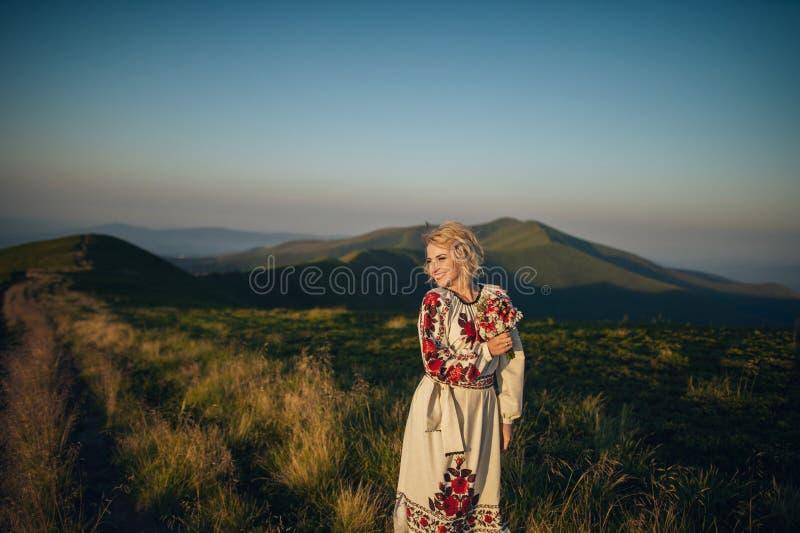 Het gelukkige paar stellen bij bergen stock afbeeldingen