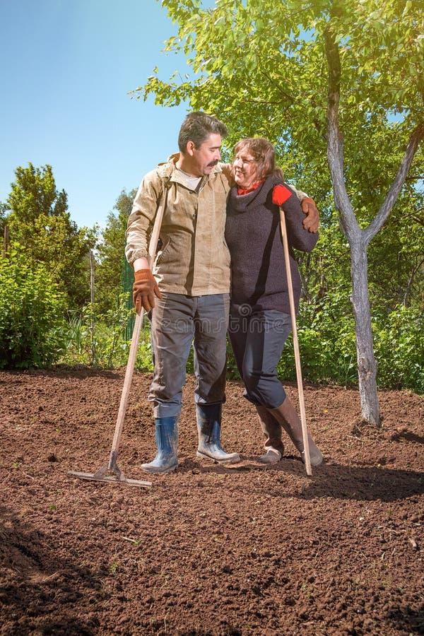 Het gelukkige paar van een familie van landbouwers op hun tuin verheugt zich op a royalty-vrije stock afbeeldingen