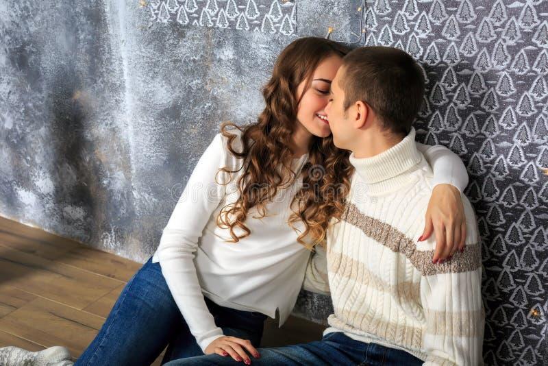 Het gelukkige paar van jongeren in liefde zit op de vloer Close-up stock afbeelding