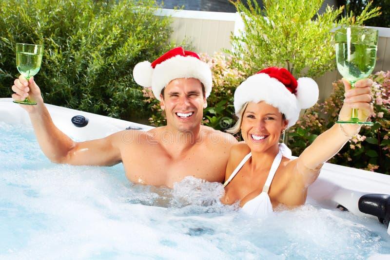 Het gelukkige paar van Kerstmissanta in Jacuzzi. stock afbeeldingen