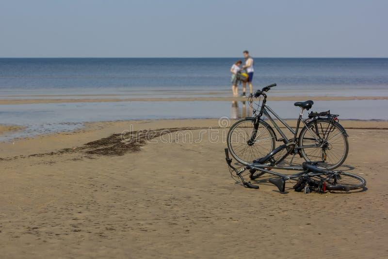 Het gelukkige paar verliet hun fietsen op het strand, dat zij van vakantieaanpassing hebben bereden stock afbeeldingen
