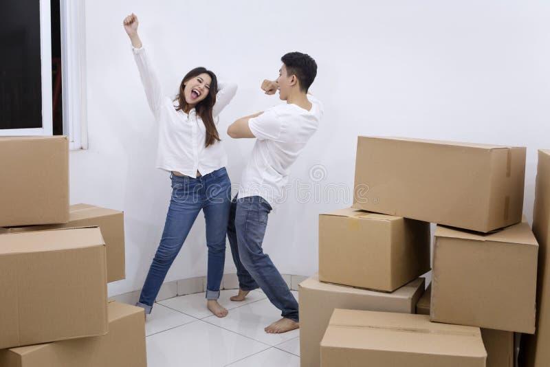 Het gelukkige paar het vieren bewegen zich in een nieuw huis stock foto's