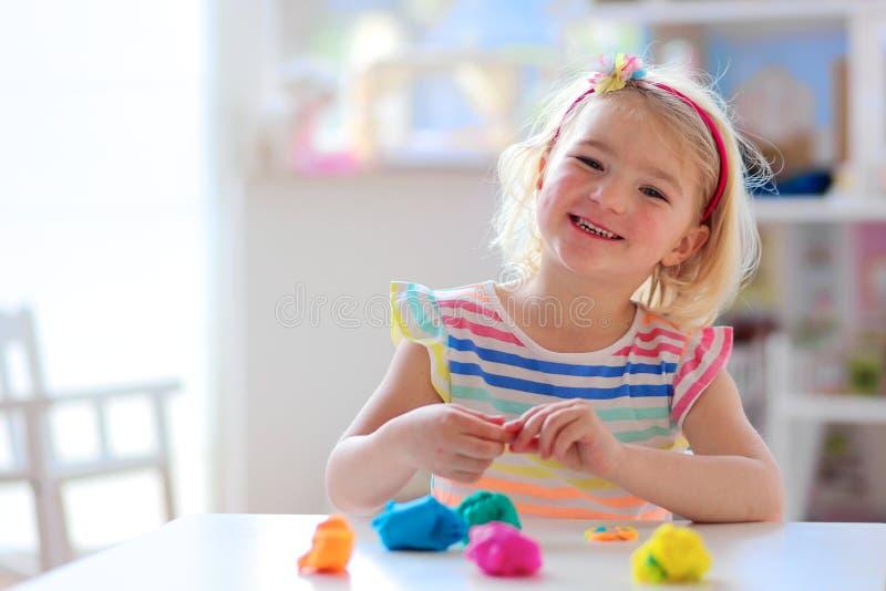 Het gelukkige peutermeisje spelen met plasticine stock foto's