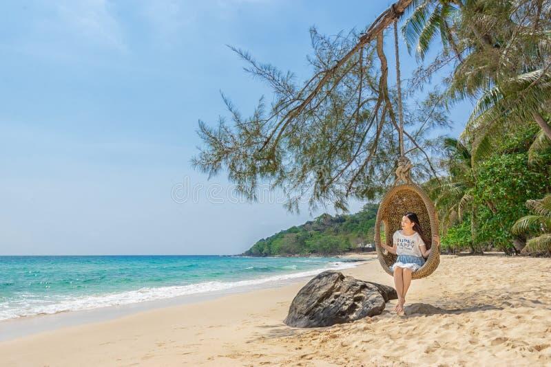 Het gelukkige reizigers Aziatische vrouw ontspannen op luxeschommeling en het kijken het mooie strand van het aardlandschap de va royalty-vrije stock afbeeldingen
