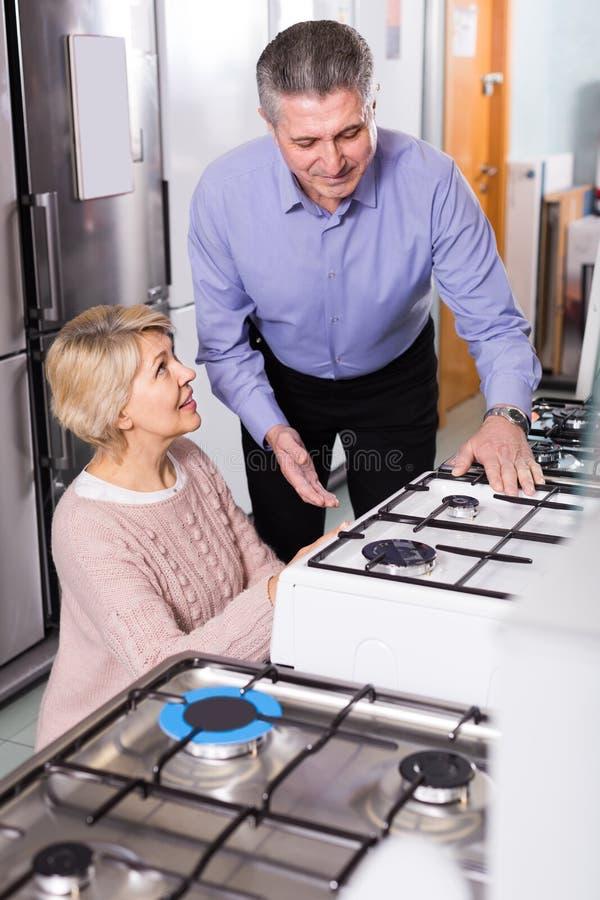 Het gelukkige rijpe paar kiest in winkel van huishoudapparatengas stock foto's
