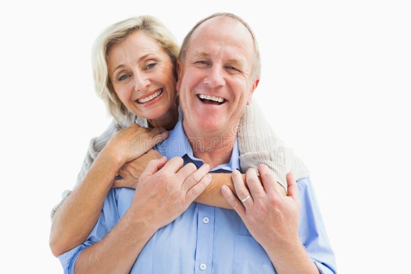 Het gelukkige rijpe paar omhelzen die bij camera glimlachen royalty-vrije stock afbeelding
