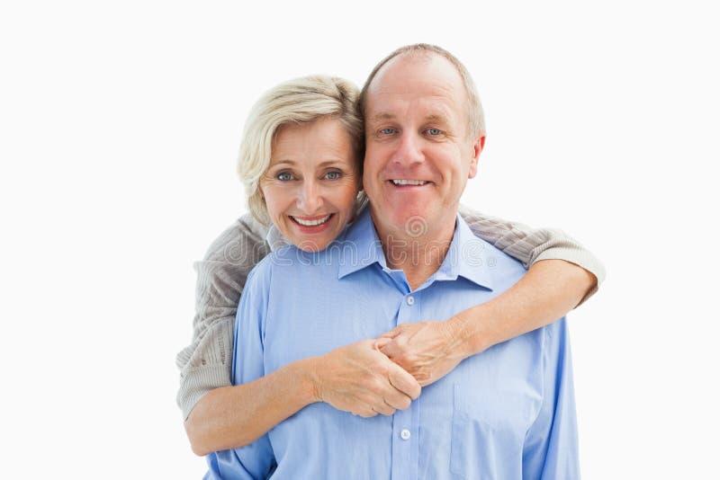 Het gelukkige rijpe paar omhelzen die bij camera glimlachen stock fotografie