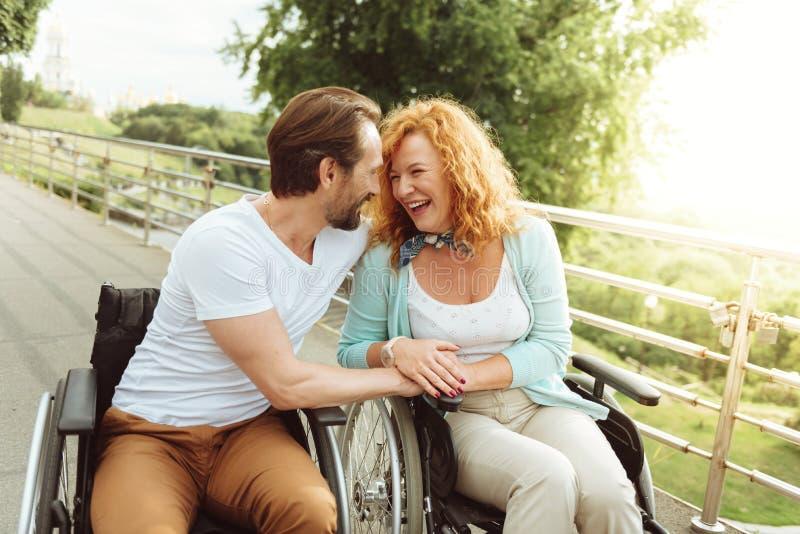 Het gelukkige rijpe paar richten in rolstoelen stock afbeelding