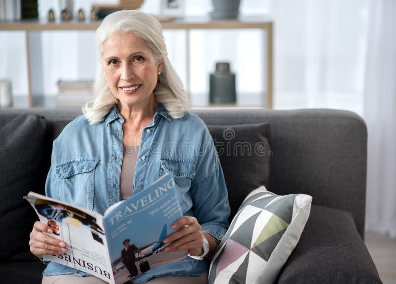 Het gelukkige rijpe tijdschrift van de vrouwenlezing in woonkamer royalty-vrije stock afbeelding