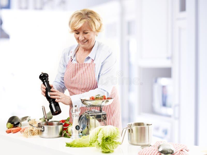 Het gelukkige rijpe vrouw koken royalty-vrije stock foto