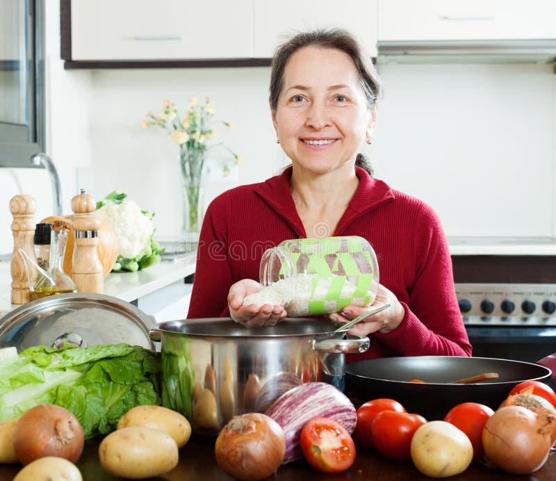 Het gelukkige rijpe vrouw koken met rijst stock afbeeldingen