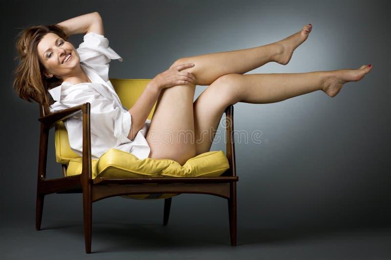 Het gelukkige rijpe vrouw ontspannen op stoel. stock afbeeldingen