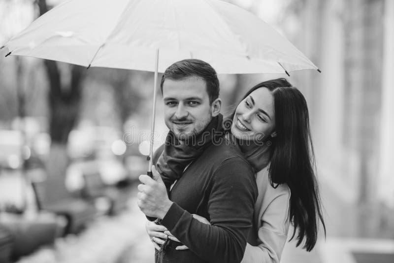 Het gelukkige romantische paar, kerel en zijn meisje de gekleed in vrijetijdskleding koesteren onder de paraplu en bekijken elk royalty-vrije stock afbeelding