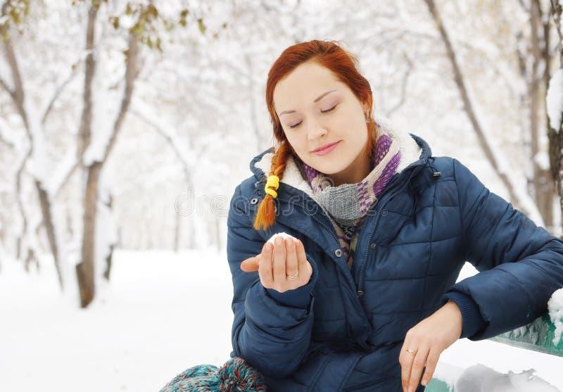 Het gelukkige roodharige mooie meisje zit op de bank in de winterpark royalty-vrije stock fotografie