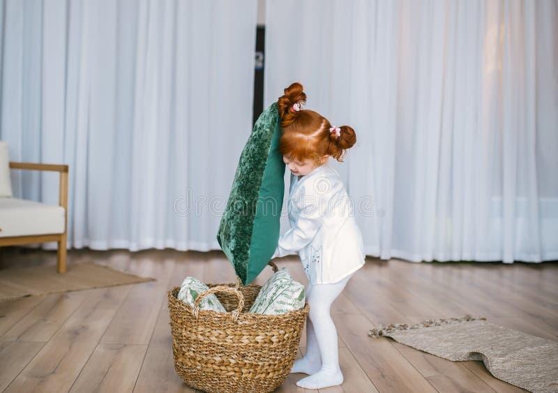 Het gelukkige roodharigemeisje in pyjama's speelt met mand en hoofdkussens thuis op vloer royalty-vrije stock afbeelding