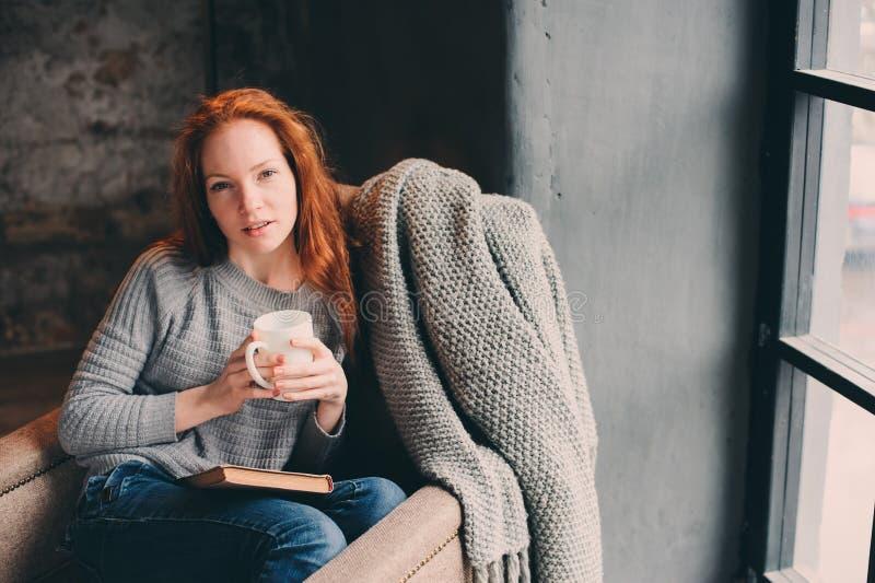 Het gelukkige roodharigevrouw ontspannen thuis in comfortabel de winter of de herfstweekend met boek en kop die van hete thee, al stock fotografie